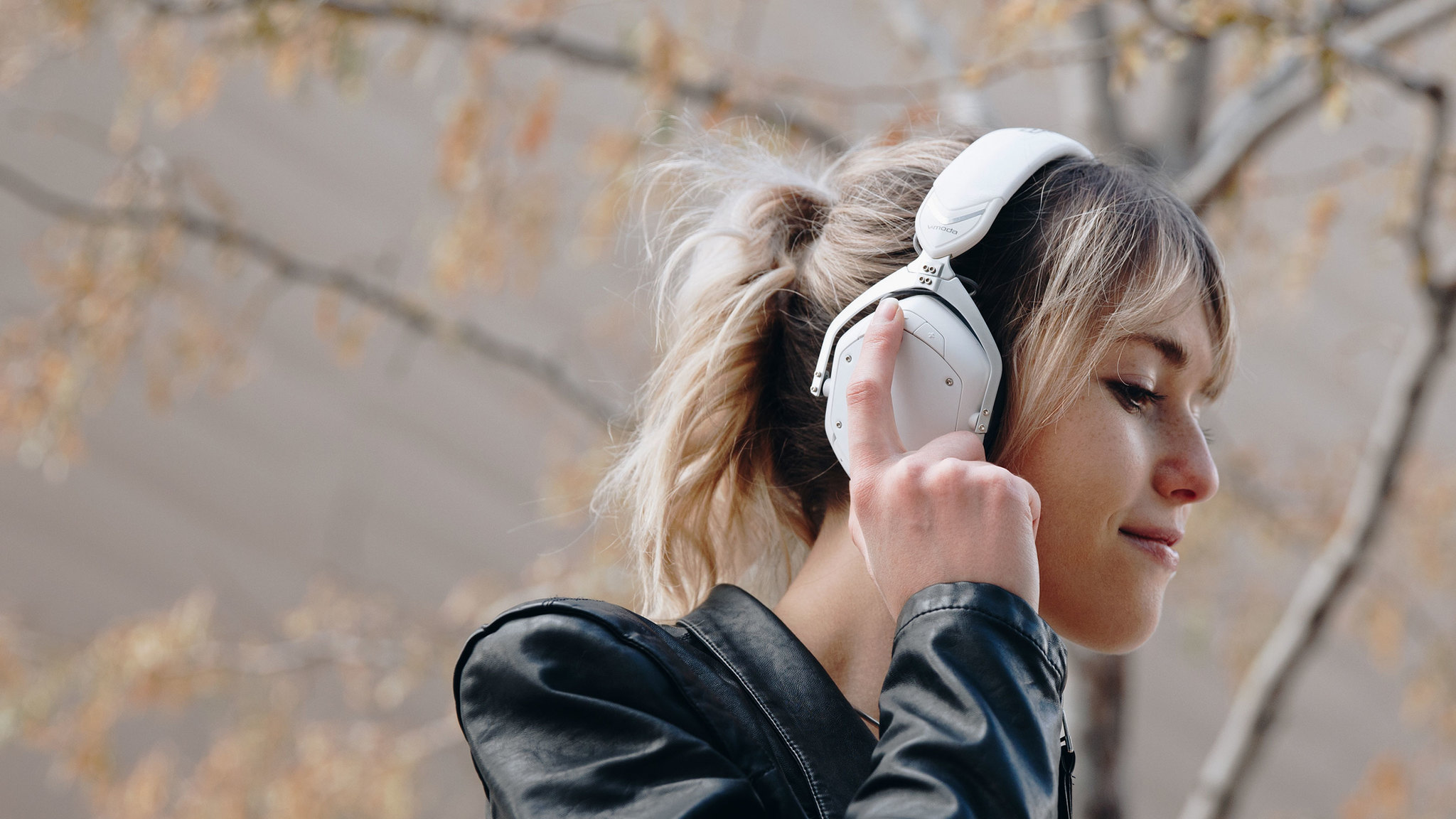 Girl using the intuitive external controls of Crossfade 2 Wireless Codex Edition Over-Ear Bluetooth Headphones in Matte White